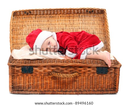 Funny picture of a little child in Santa Claus costume sleeping in a vintage gift box.