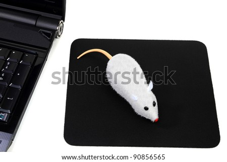 Funny picture of computer accessories, a mouse toy as two button wireless mouse over black mouse pad and corner of laptop computer, all over white background. - stock photo