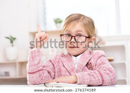 Funny picture of girl playing role of business woman. Girl wearing suit and glasses. Girl sitting at table with notebook, looking at camera with her point finger up. Office interior as a background - stock photo
