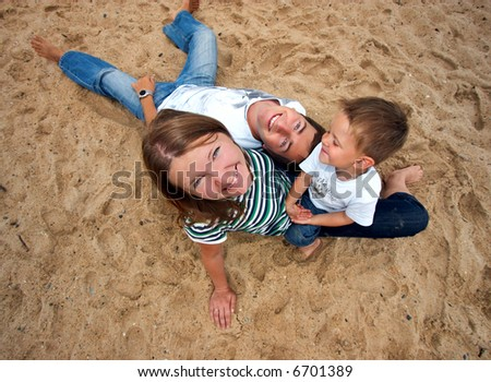 Funny picture of happy young family of three - stock photo