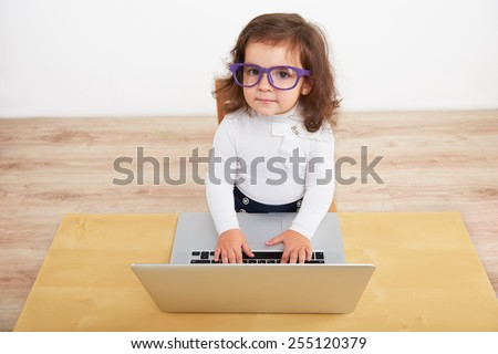 Funny picture of little beautiful girl pretending to be business woman. Girl wearing glasses and working on the laptop - stock photo