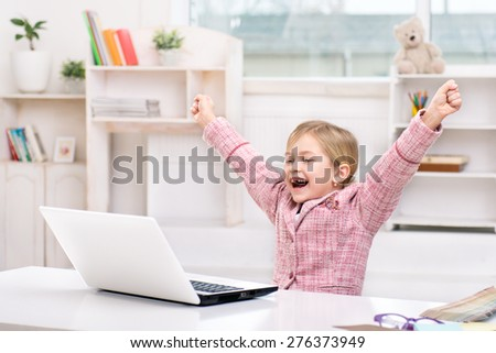 Funny picture of little cute girl playing role of business woman. Girl wearing pink suit. Girl sitting at table, cheerfully looking at laptop and showing success. Office interior as a background - stock photo