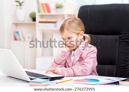 Funny picture of little cute girl playing role of business woman. Girl wearing pink suit. Girl sitting at table on large office chair and discontentedly using laptop. Office interior as a background - stock photo
