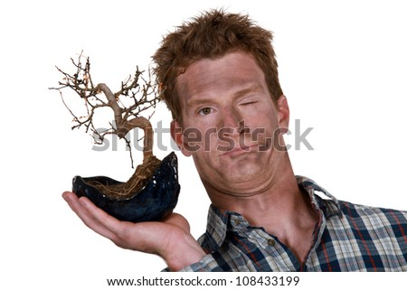 funny picture of man holding bonsai after explosion - stock photo