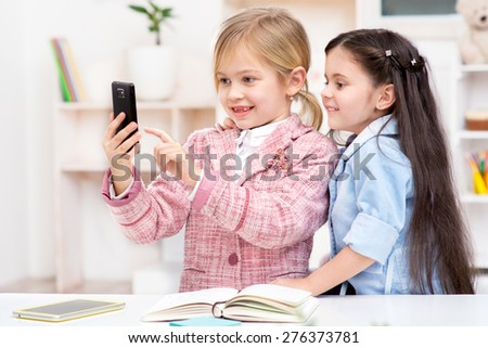 Funny picture of two little cute girls playing role of business women. Girls smiling and making photo by phone. Office interior as a background - stock photo