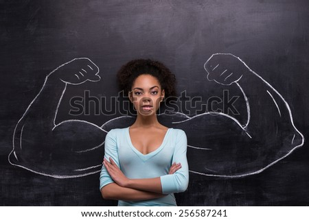 Funny picture of young afro-american woman on chalkboard background seriously looking at camera. Two strong muscular arms painted on chalkboard - stock photo