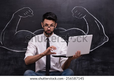 Funny picture of young businessman with laptop on chalkboard background. Two strong muscular arms painted on chalkboard - stock photo
