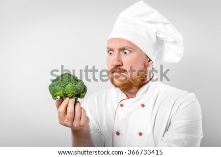 Funny picture of young male chef in white uniform. Head-cook looking at broccoli with bulging eyes. Standing against grey background - stock photo