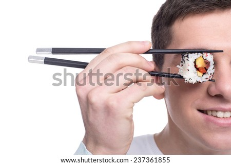 Funny picture of young man is holding piece of sushi rolls on his eye. Isolated on white background. Close-up. - stock photo
