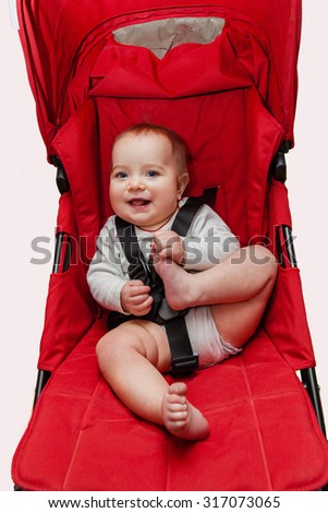 Funny playful baby sitting in his new red stroller. Child feeling happy, playing with his legs. Raised back, fasten seat belts. Safety first concept. Selective focus on baby head.  - stock photo