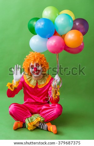Funny playful clown in orange wig holding balloons, waving, looking at camera and smiling, sitting on a green background