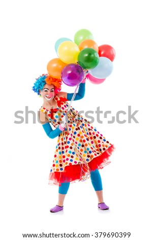 Funny playful female clown in colorful wig holding balloons, looking at camera and smiling, isolated on a white background - stock photo