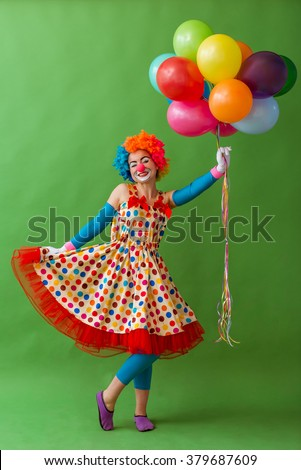 Funny playful female clown in colorful wig holding balloons, posing, looking at camera and smiling, standing on a green background - stock photo