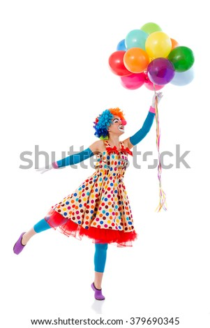 Funny playful female clown in colorful wig holding balloons, standing on one leg like ready to fly, isolated on a white background - stock photo