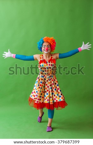 Funny playful female clown in colorful wig keeping hands apart, looking at camera and smiling, standing on a green background - stock photo