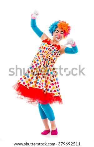 Funny playful female clown in colorful wig showing not OK sign, looking at camera and smiling, isolated on a white background - stock photo