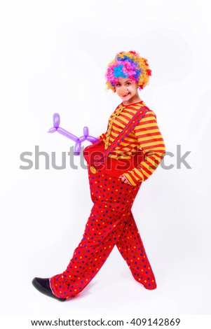Funny playful girl clown in colorful wig holding a balloon dog, isolated on a white background. Clown in the costume - stock photo