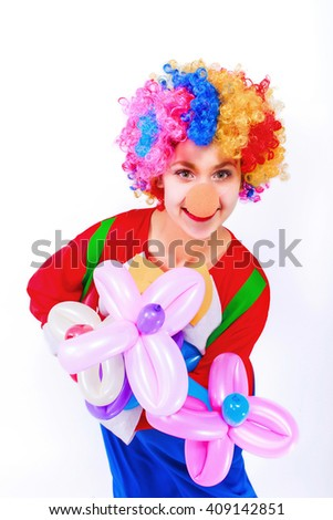 Funny playful girl clown in colorful wig holding a balloon flowers, isolated on a white background. Clown in the costume - stock photo