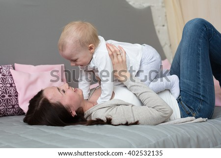 Funny playful mum with baby toddler at home, Funny baby with mother - stock photo