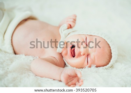 funny portrait dreamy  little baby (child, kidd, infant) cry   lying in a carpet. newborn. son. boy. - stock photo