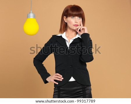funny portrait of a beautiful, young businesswoman, with a light bulb, thinking, on beige background - stock photo