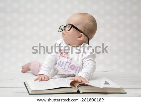 Funny portrait of a cute baby girl in glasses lying over a big book - stock photo