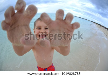 Funny portrait of a cute Caucasian boy standing in shallow water on a tropical beach. Fisheye lens exaggerated portrait.