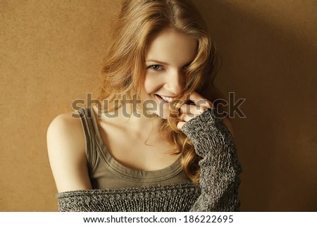 Funny portrait of a fashionable model with long red curly hair in gray sweater posing over wooden background. White shiny smile. Hipster style. Daylight. Close up. Copy-space. Studio shot