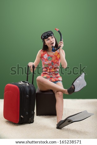 Funny portrait of a girl dreaming of a vacation with her travel luggage and snorkeling equipment, on green background - stock photo