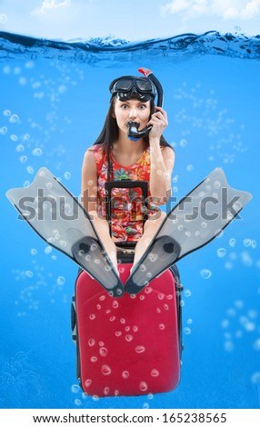 Funny portrait of a girl with her travel luggage and snorkeling equipment sitting under the water - stock photo