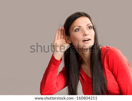 ... portrait of a listening young woman on gray background - stock photo