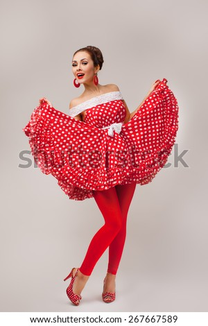 Funny portrait of a smiling cute young female model wearing red dress - stock photo