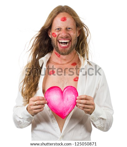 Funny portrait of a very happy hippie man covered in red lipstick kisses and holding a love heart - stock photo