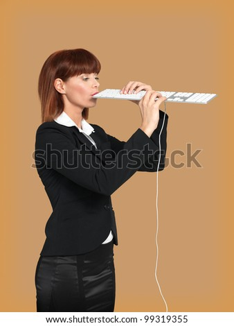 funny portrait of a young businesswoman, playing and singing on a computer keyboard, on beige background - stock photo