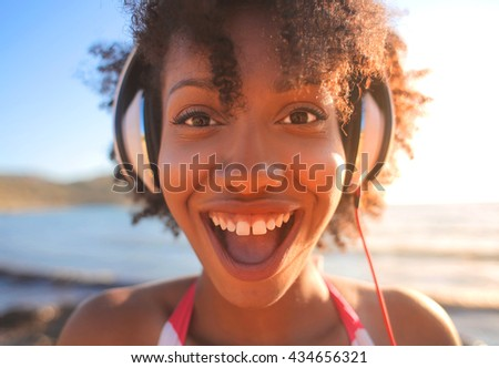 Funny portrait of a young girl listening music with her headphones in vacation at the sea - stock photo