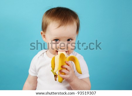 Funny Portrait of a young girl with lemon slices over her eyes on a blue studio background - stock photo