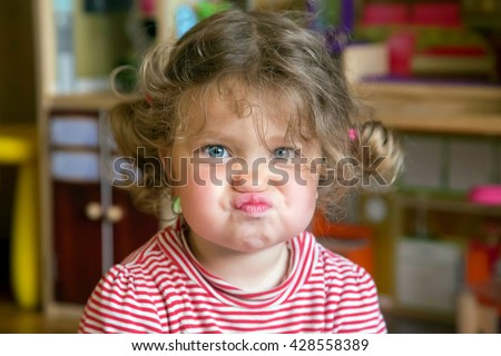 Funny portrait of adorable baby girl. Child makes grimaces face - stock photo