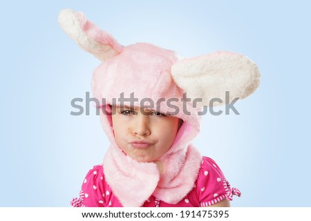Funny portrait of an unhappy, pouting, little girl in pink bunny costume - stock photo