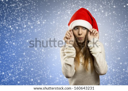 funny portrait of attractive young woman with long smooth hair, warm sweater and red santa claus hat