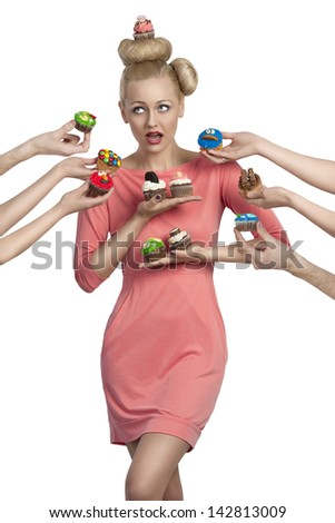 funny portrait of blonde girl with strange hair-style and colorful make-up  surrounded by some hands with cupcakes - stock photo