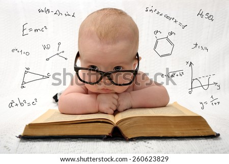 funny portrait of cute baby in glasses lying on old book and thinking of all the knowledge in the world - stock photo