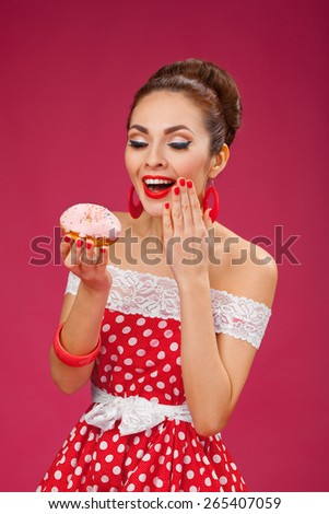 Funny portrait of cute young female model with sweet food in her arms wearing red dress - stock photo