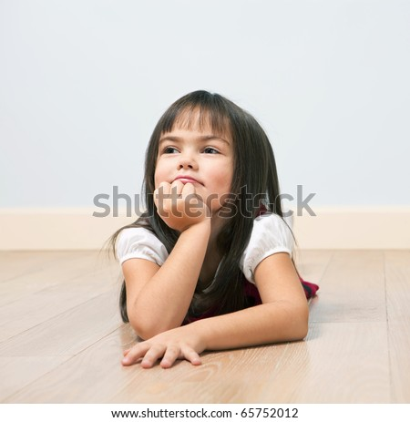 Funny portrait of lying cute girl on a wooden floor indoors - stock photo