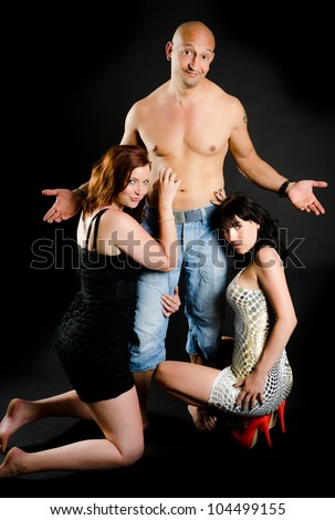 Funny portrait of man with bare chest and two beautiful girls adoring him