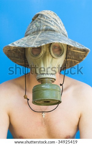 funny portrait of man with gas mask against blue background
