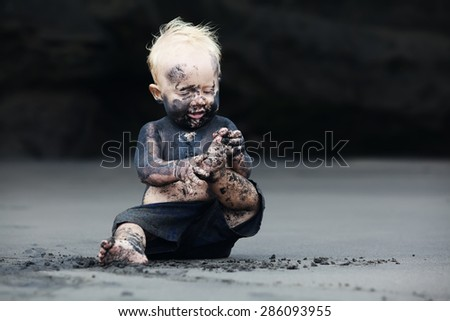 Funny portrait of smiling child with dirty face sitting and playing with fun on black sand sea beach before swimming in ocean. Family active lifestyle, and water leisure on summer vacation with baby - stock photo
