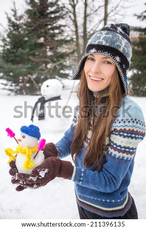Funny portrait of winter girl with little snowman. focus on woman - stock photo