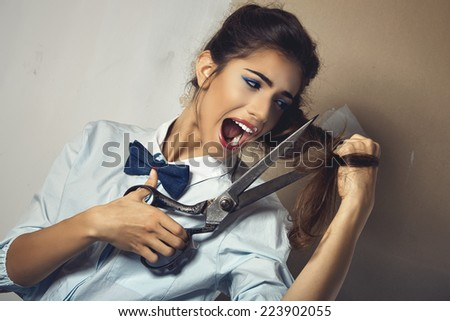Funny portrait of young sexy woman tries to cut his long hair with a huge scissor - stock photo