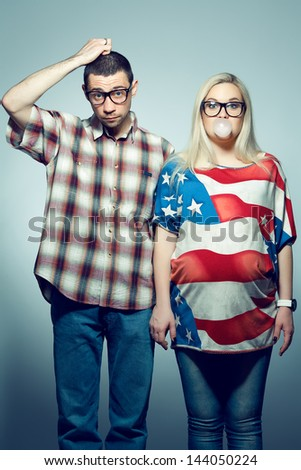 Funny pregnancy concept: portrait of two hipsters (husband and wife) in trendy glasses and clothes posing over gray background. Studio shot