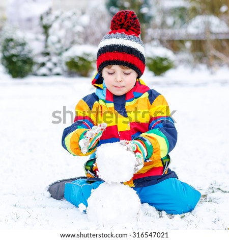 Funny preschool boy in colorful clothes making a snowman, playing and having fun with snow, outdoors  on cold day. Active outdoors leisure with children in winter. - stock photo